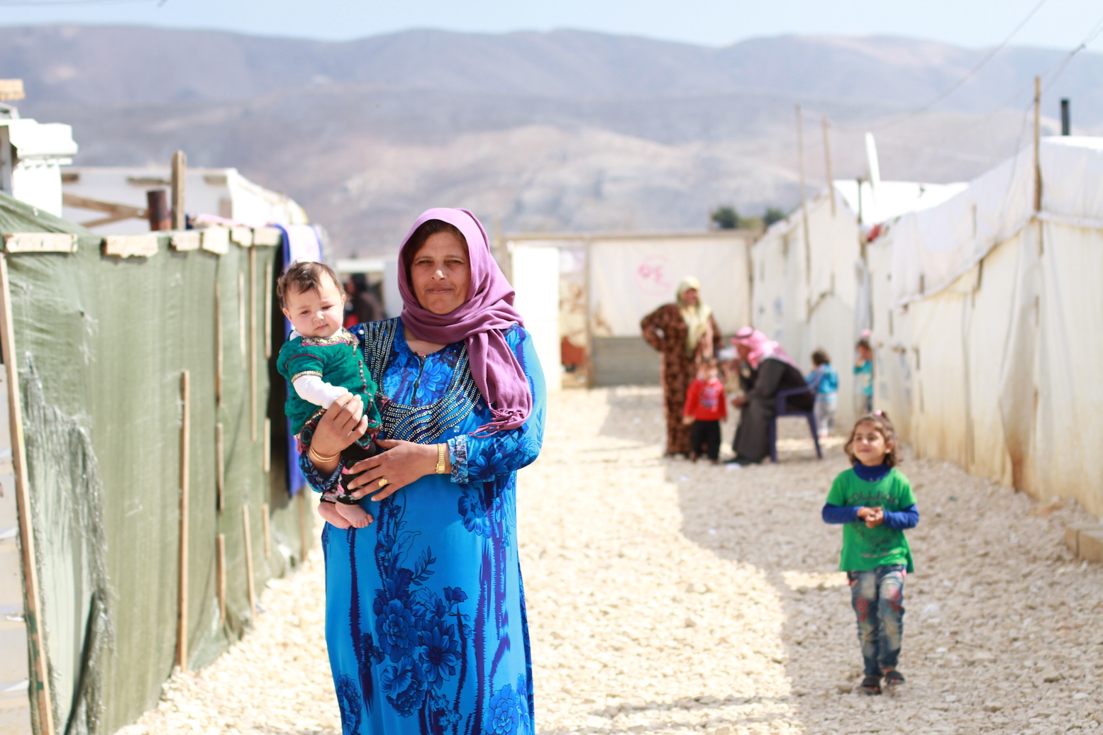 A refugee woman holds her child in an informal settlement in the town of Dalhamiye in Lebanon's Bekaa. The informal settlement, situated between Mount Lebanon to the West and the Anti-Lebanon Mountains to the East, is home to 70 Syrian families most of whom are originally from Homs.